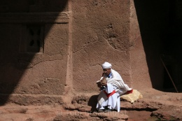 The reader. This clergyman contemplates outside one of Lalibela's rock-hewn churches. Copyright Tom Broadhurst.