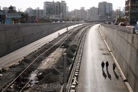 People walk past the construction of Addis Ababa's new light rail system in 2014. Copyright Tom Broadhurst.
